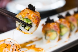 Sushi roll with black chopsticks