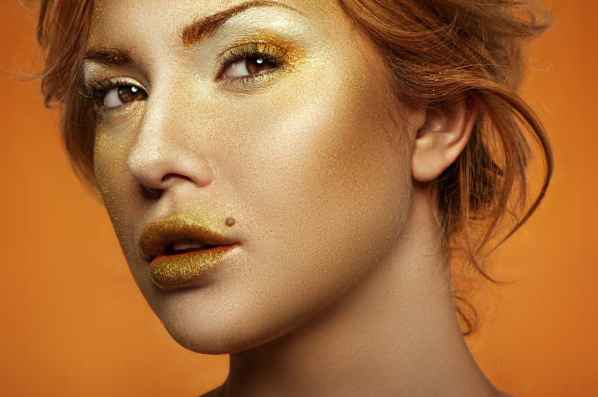 Fashion Model with golden Makeup on Face and Lips